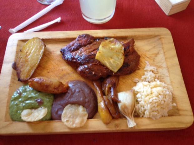 Traditional Mayan lunch, with roasted pork, tamales, rice, guacamole, refried beans, rice and potato.