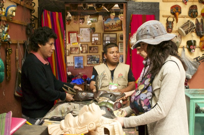 Miguel Ignacia, the mask maker, left, with our Chichicastenango guide Sebastian, center, and Deborah (front) and Crit (behind Deborah) shopping for masks.