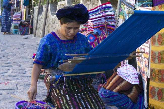 A woman weaving a hiupul in Santa Catarina, wearing a blue hiupul, which is common to the woman of the town