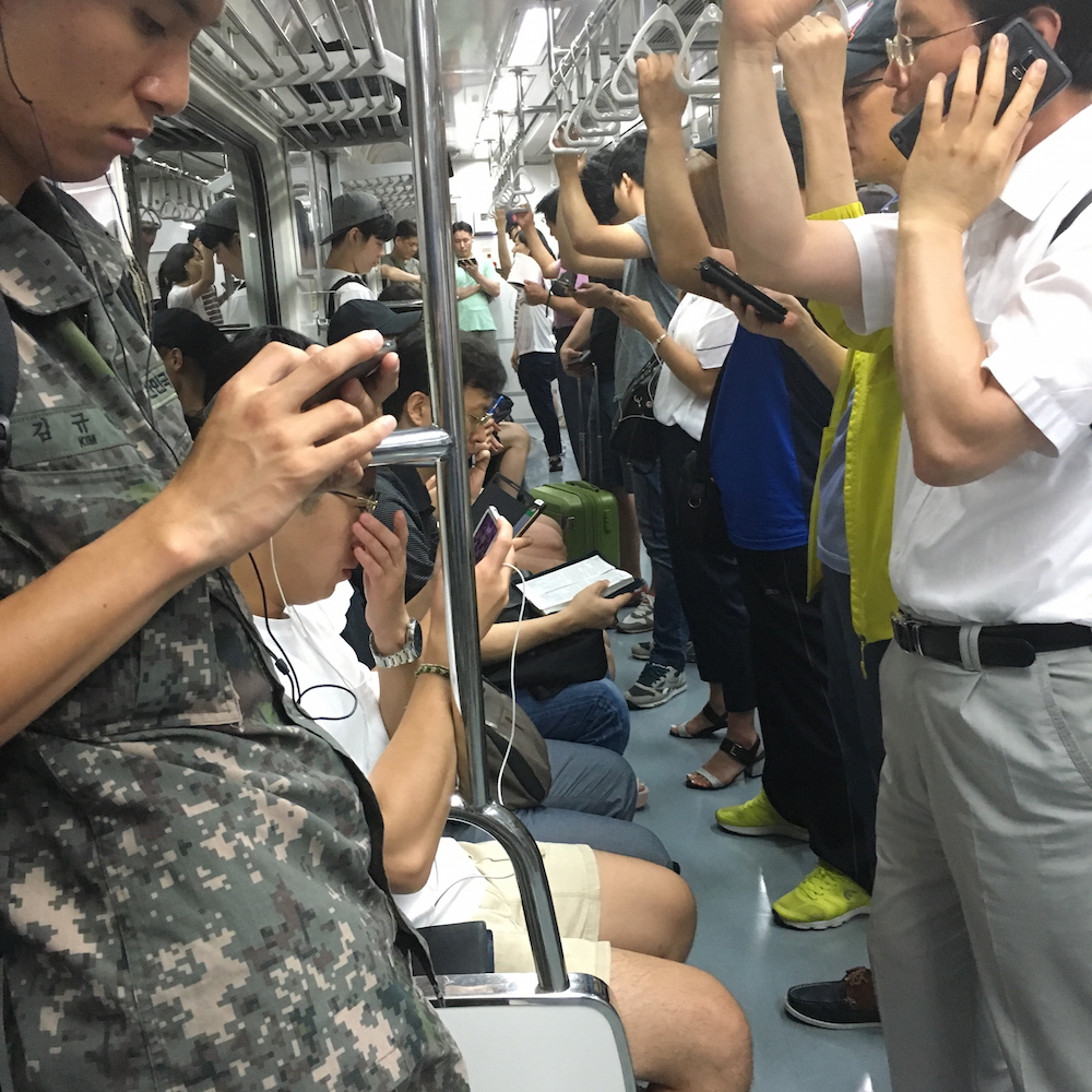 In a subway car in Seoul, nearly everyone is one a mobile device, except for one man who is reading a Bible