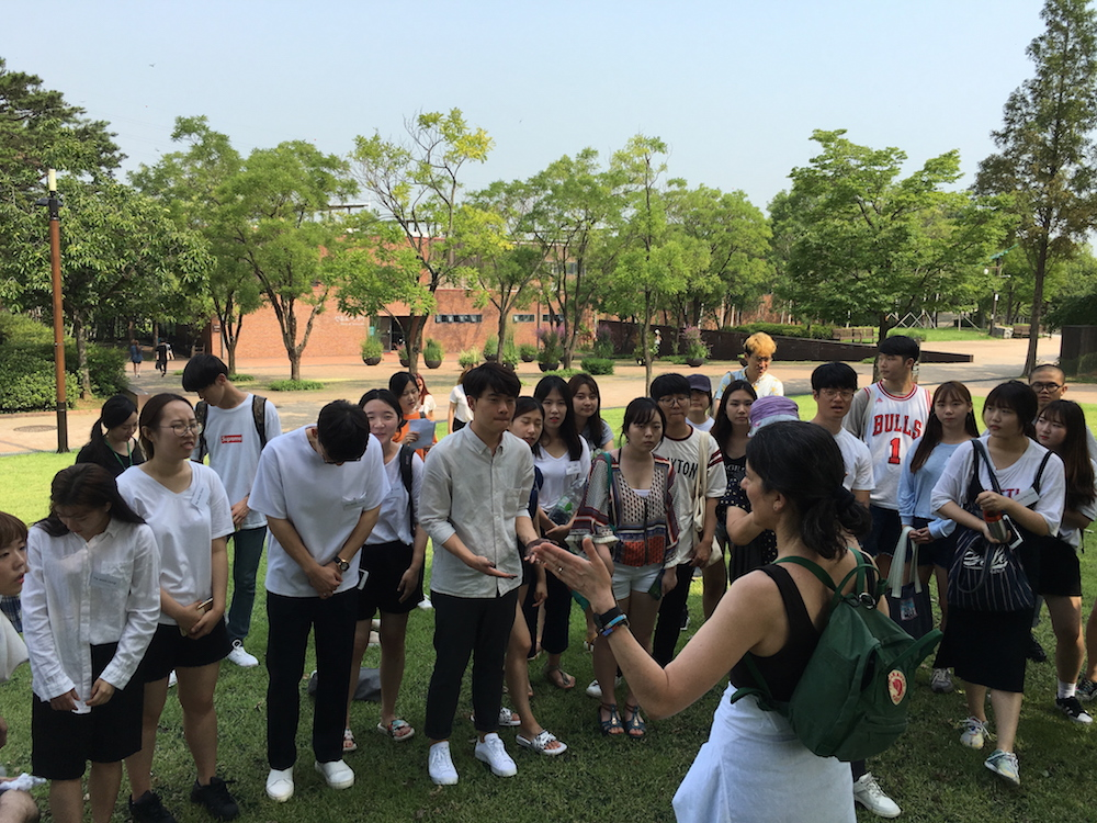 Deborah Zlotsky speaks to a group of Samsung Art and Design Institute students in the shade of a tree, Seonyudo Park, Seoul, South Korea