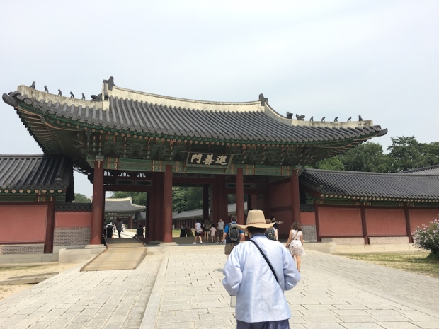 A tour guide in traditional clothes and straw hat leads visitors toward the Main gate of Changdeokgung Palace