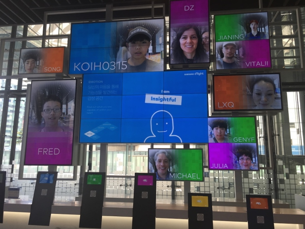 A wall of screens at the Samsung D-light Store, Seoul, South Korea, shows names and faces of visitors, including Deborah and Michael