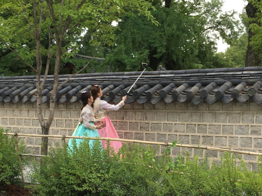 Two young women in traditional costume visit the traditional Hanok Village in Jeonju, South Korea, and take selfies with a selfie stick